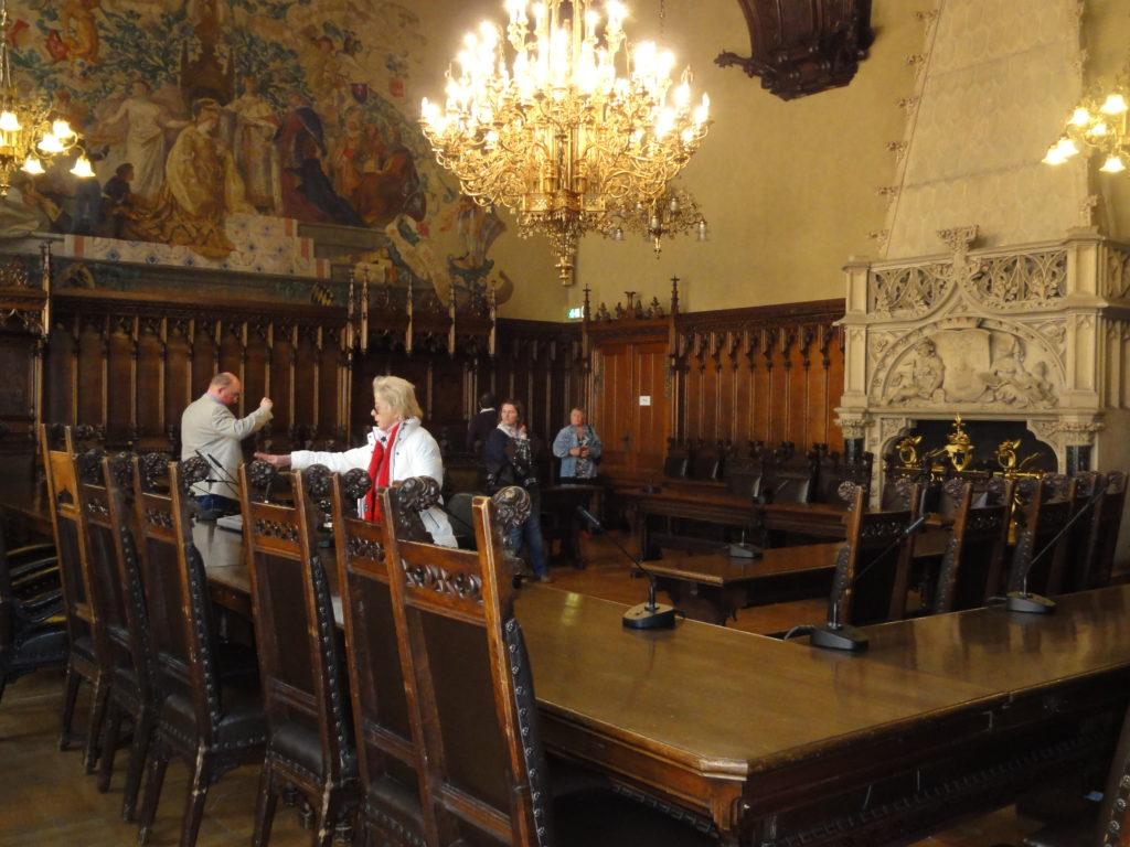 Der Kleine Sitzungssaal ist noch original. Das wertvolle Mobiliar ist aus Eiche geschnitzt. Das Wandgemälde zeigt König Ludwig I. und die vor ihm knieden Monachia